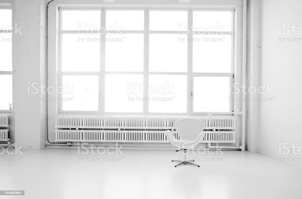 A modern white living space with a white chair royalty-free stock photo