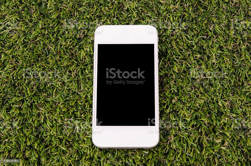 Modern white mobile phone on grass stock photo