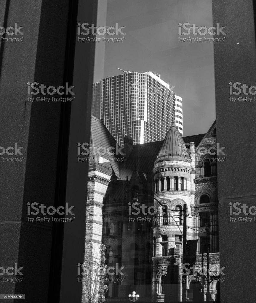 modern window reflecting image of old architecture stock photo