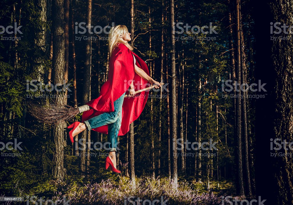 Modern witch blond in jeans and red cape flying on stock photo