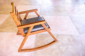 Modern wooden rocking chair on colored cement floor
