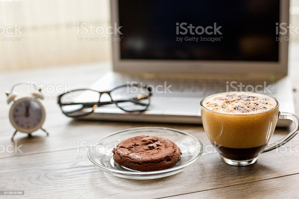 Modern working desk with laptop coffee and alarm clock stock photo