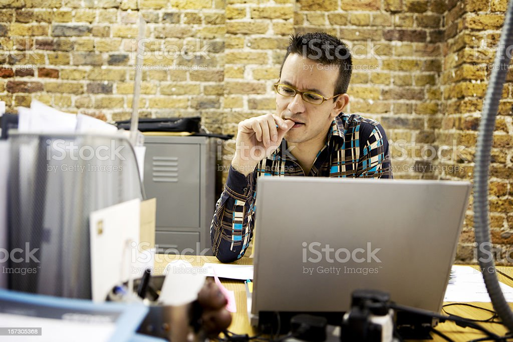 modern workplace: creative professional resolving a problem at his desk stock photo