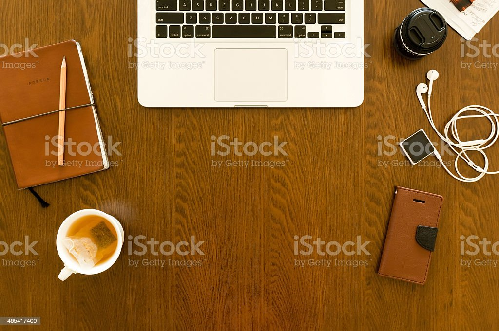 Modern workspace with laptop, smartphone, mug, and gadgets stock photo