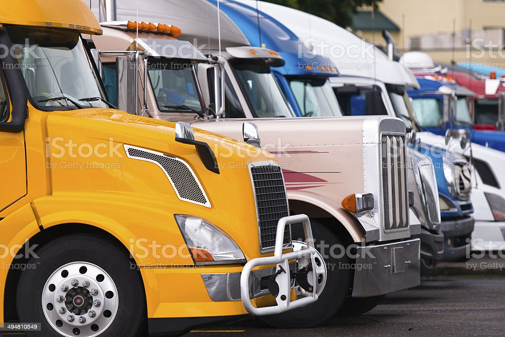 Modern yellow semi truck on foreground of other trucks stock photo