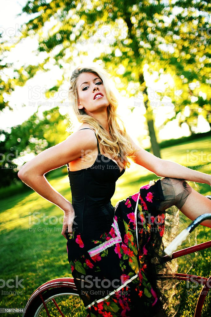 Modern Young Blonde Sitting on Red Bike royalty-free stock photo