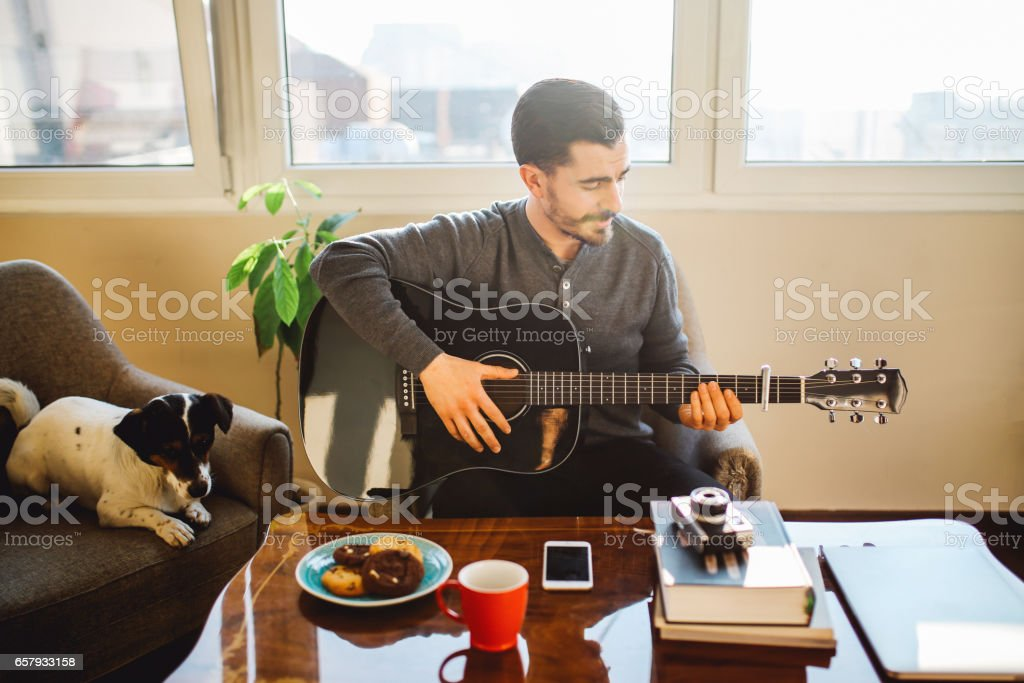 Modern young man practicing guitar at home stock photo