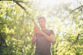 Modern young man with mobile phone in forest