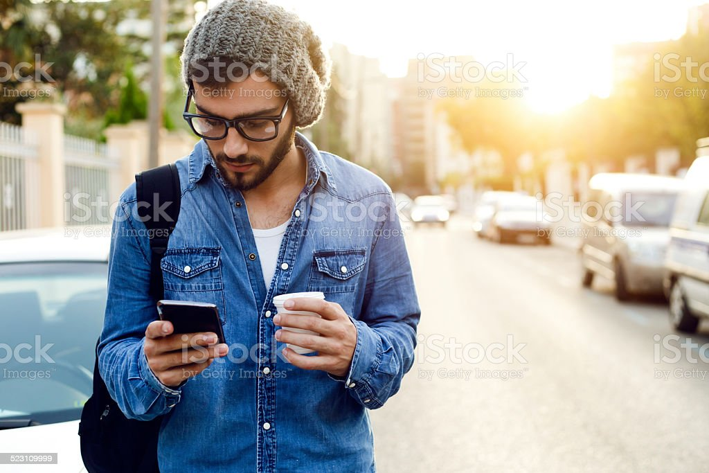 Modern young man with mobile phone in the street. stock photo