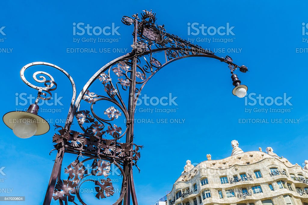 Modernist style streetlight and La Pedrera, Barcelona stock photo