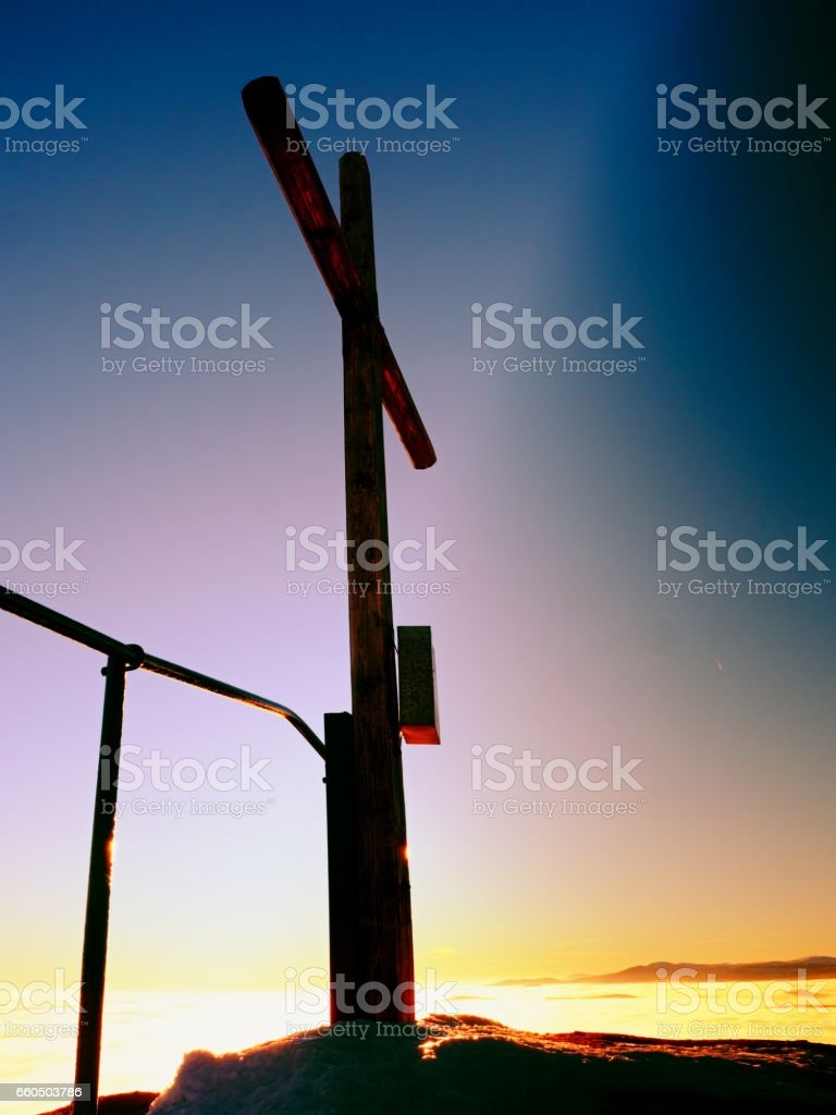 Modest wooden cross on rocky summit. Memory of victims stock photo