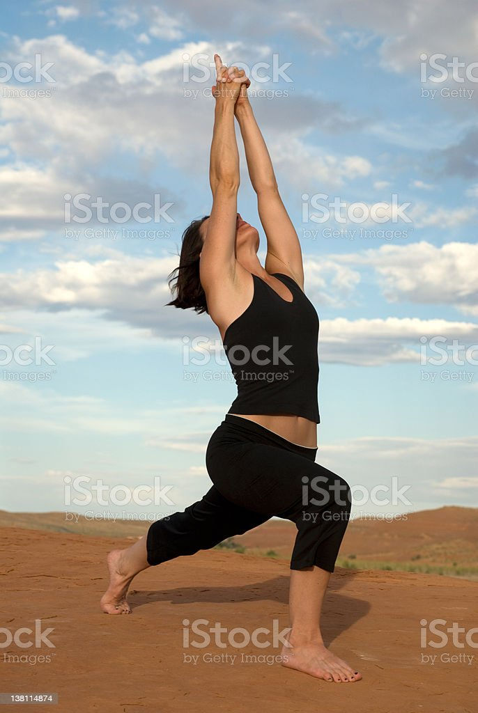 Modified Crescent Lunge Yoga Pose on Utah's Red Rocks royalty-free stock photo