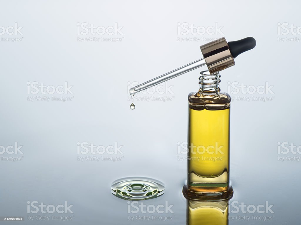 Moisturizing cosmetic oil stands on the dark water background stock photo