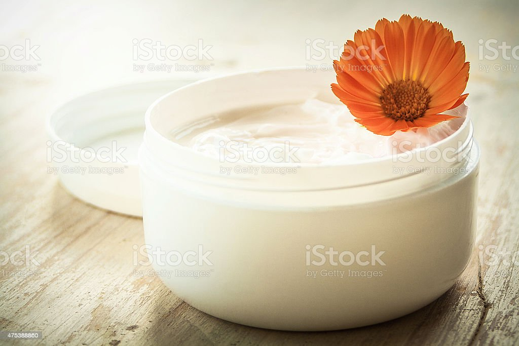 Moisturizing cream and marigold flower stock photo