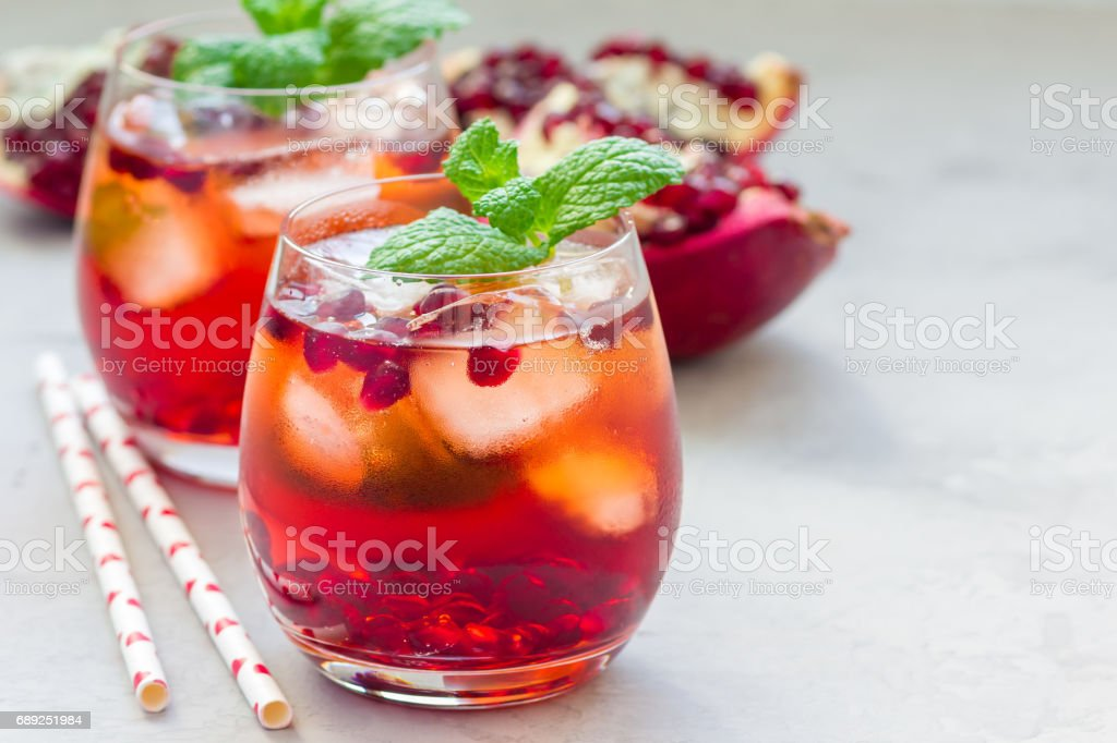 Mojito cocktail with pomegranate, mint, lemon juice and ice in glass, horizontal, copy space stock photo