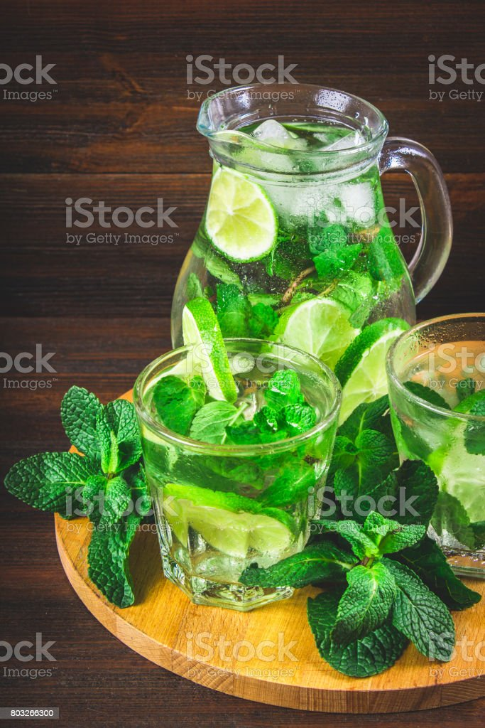 Mojito with mint and lime in a glass and a jug on the round boar stock photo