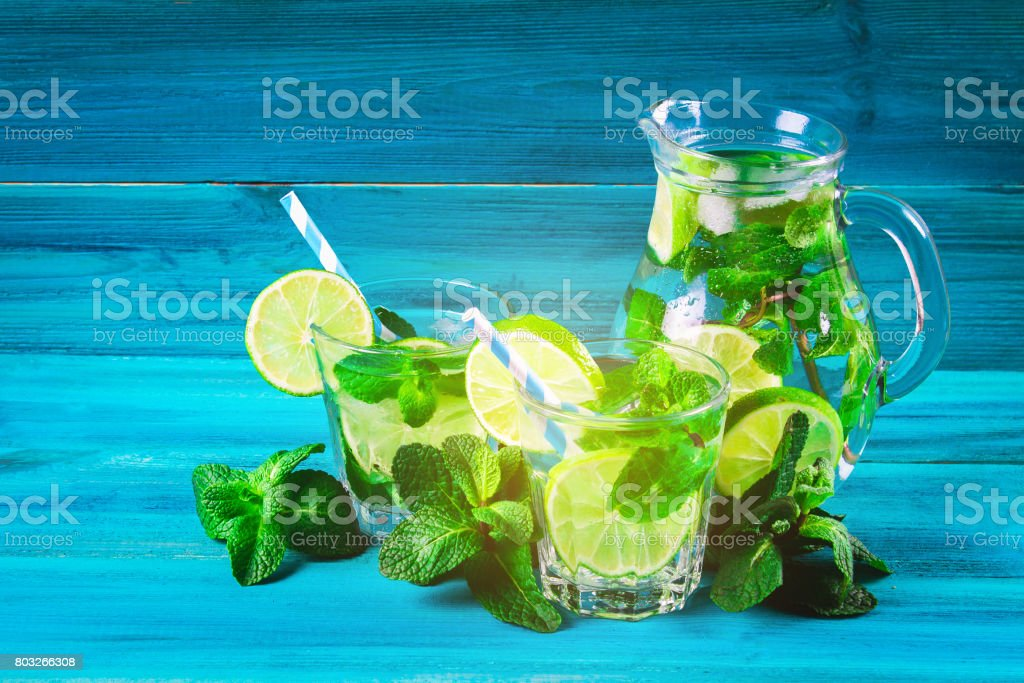 Mojito with mint and lime in a glass and a jug with tubes. Blue stock photo