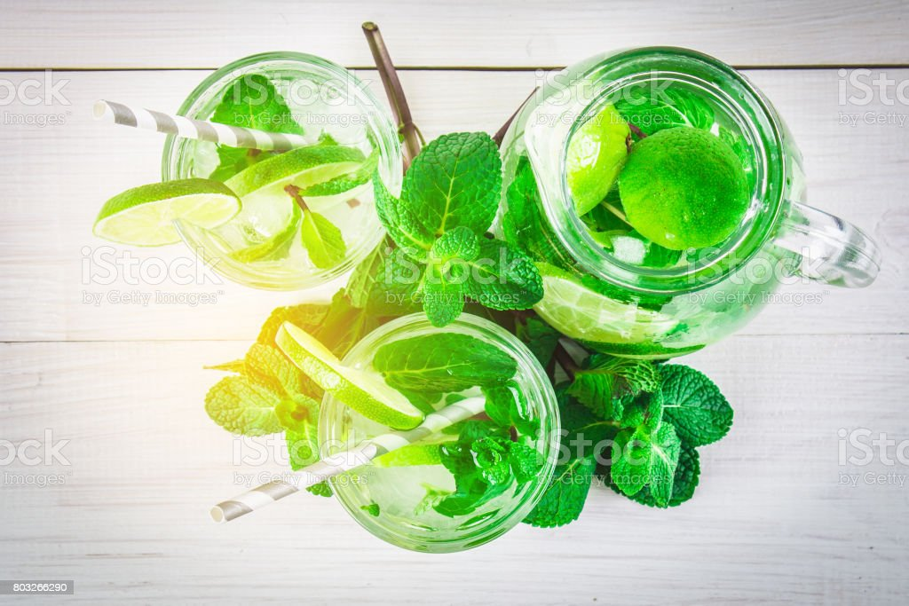 Mojito with mint and lime in a glass and a jug with tubes. White stock photo