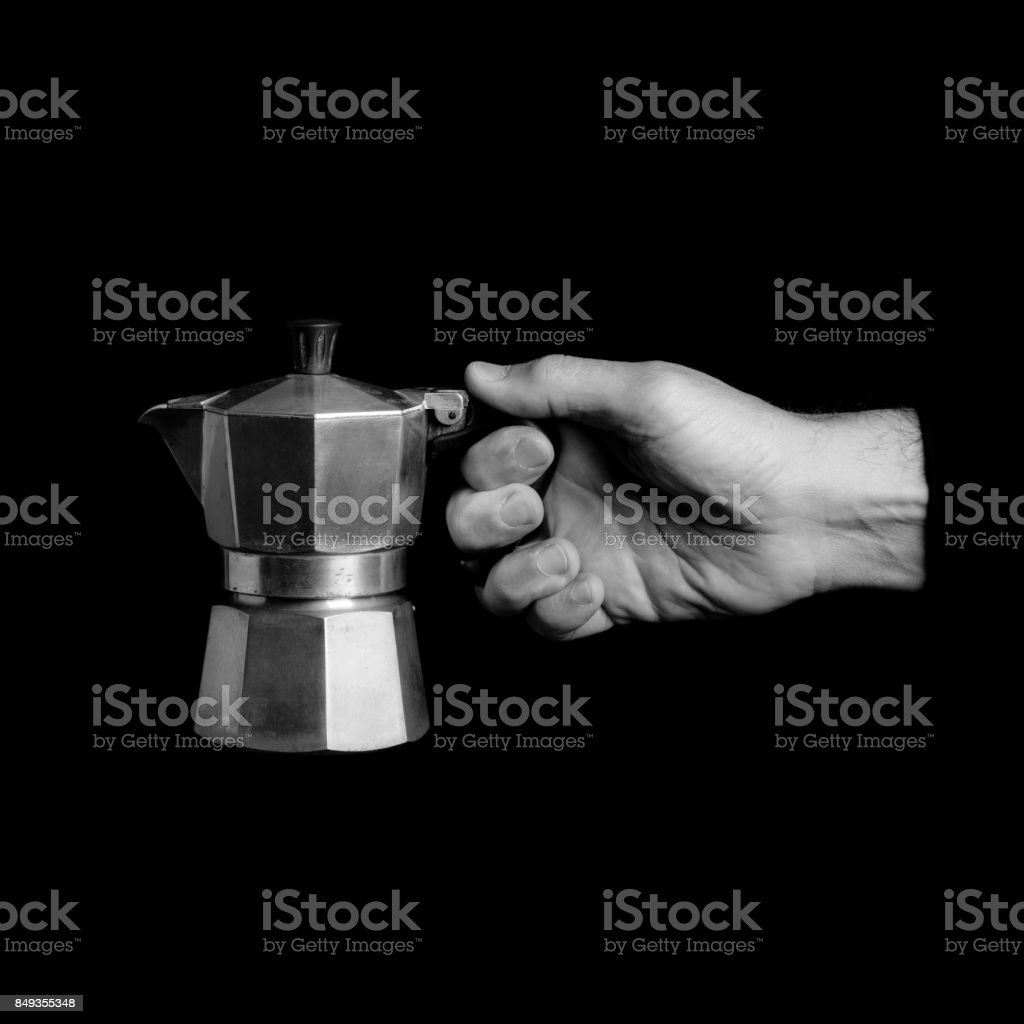 moka - kitchen tools in a man's hand - black and white photo stock photo