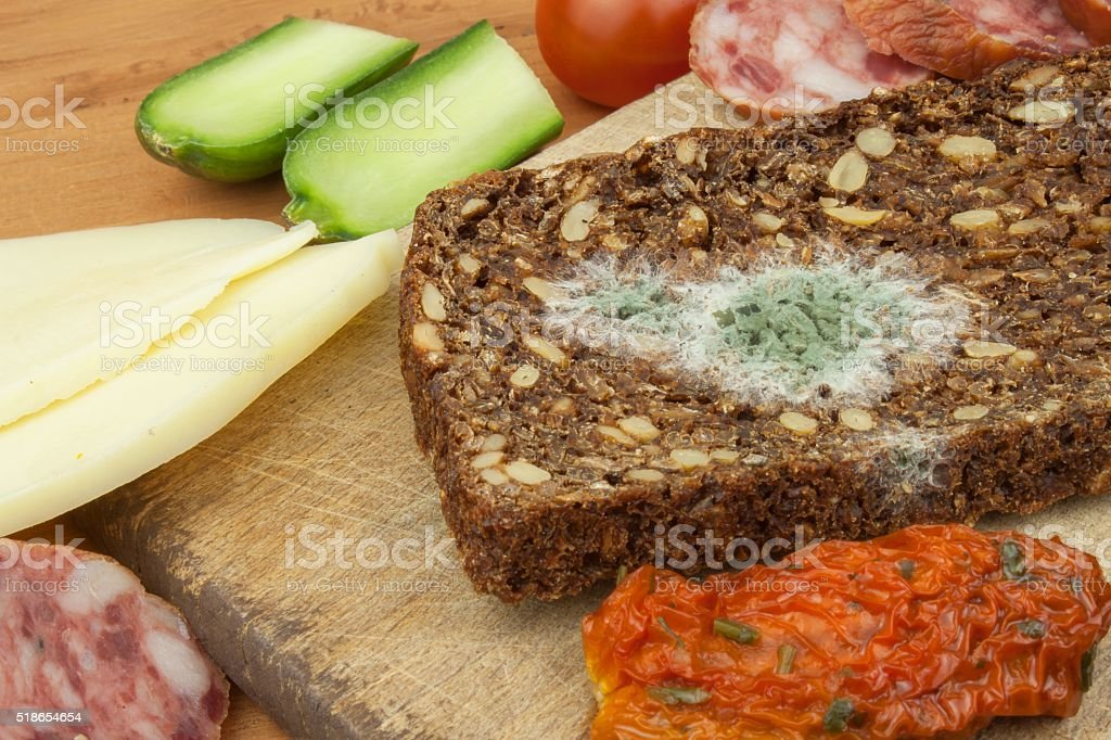 Moldy bread in wooden table. Unhealthy food. Spoiled food. stock photo