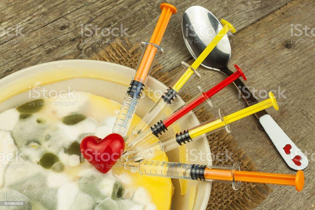 Moldy pudding and syringe. Treatment of the disease stock photo