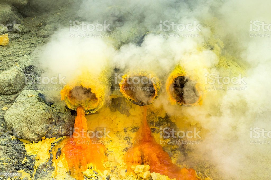 Molten Sulfur Dripping from Pipes at Ijen Volcano, Java, Indonesia stock photo
