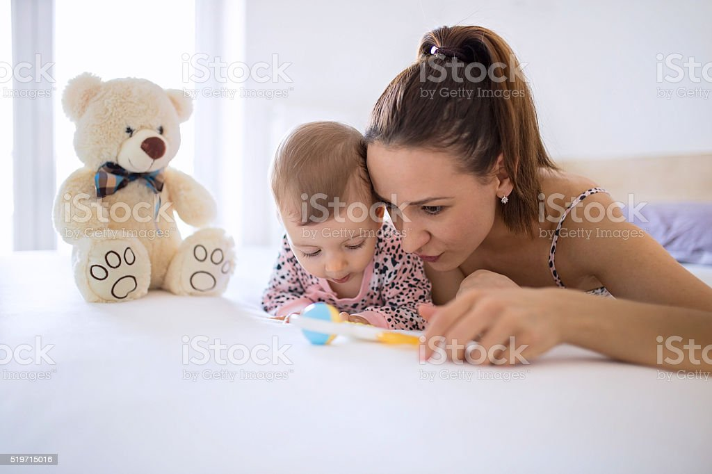 Mom and baby having fun and playing in bedroom stock photo