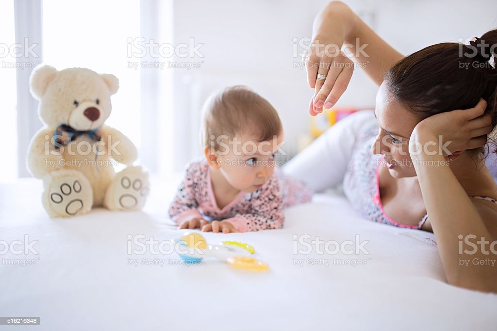 Mom and baby having fun in bedroom stock photo
