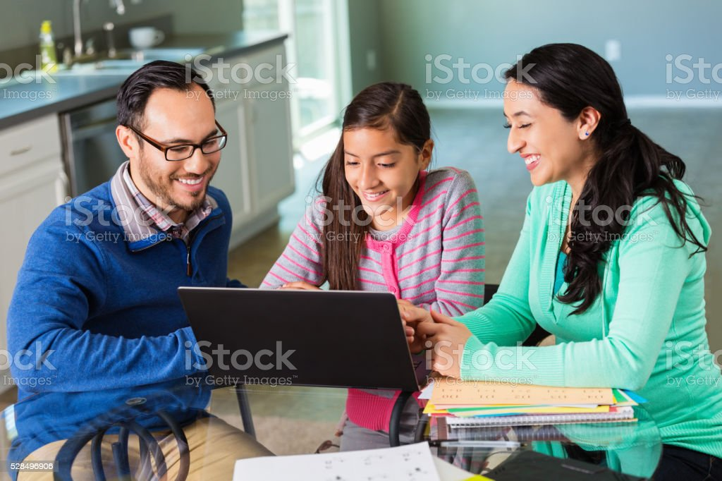 Mom and dad help daughter with homework assignment stock photo