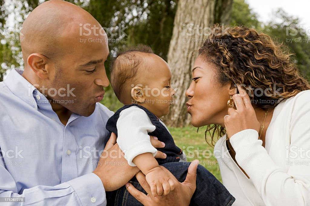 A mom and dad playing with their baby royalty-free stock photo