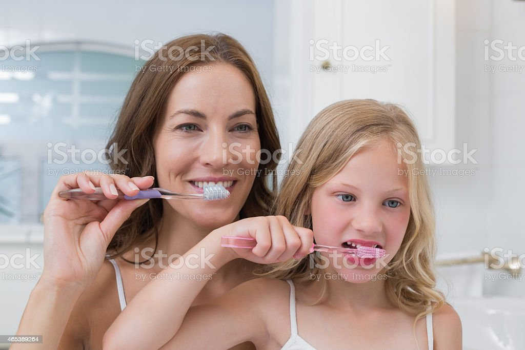 Mom and daughter brushing their teeth together stock photo