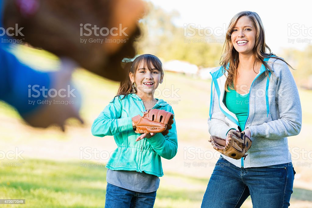 Mom and daughter catching baseball with dad at park royalty-free stock photo