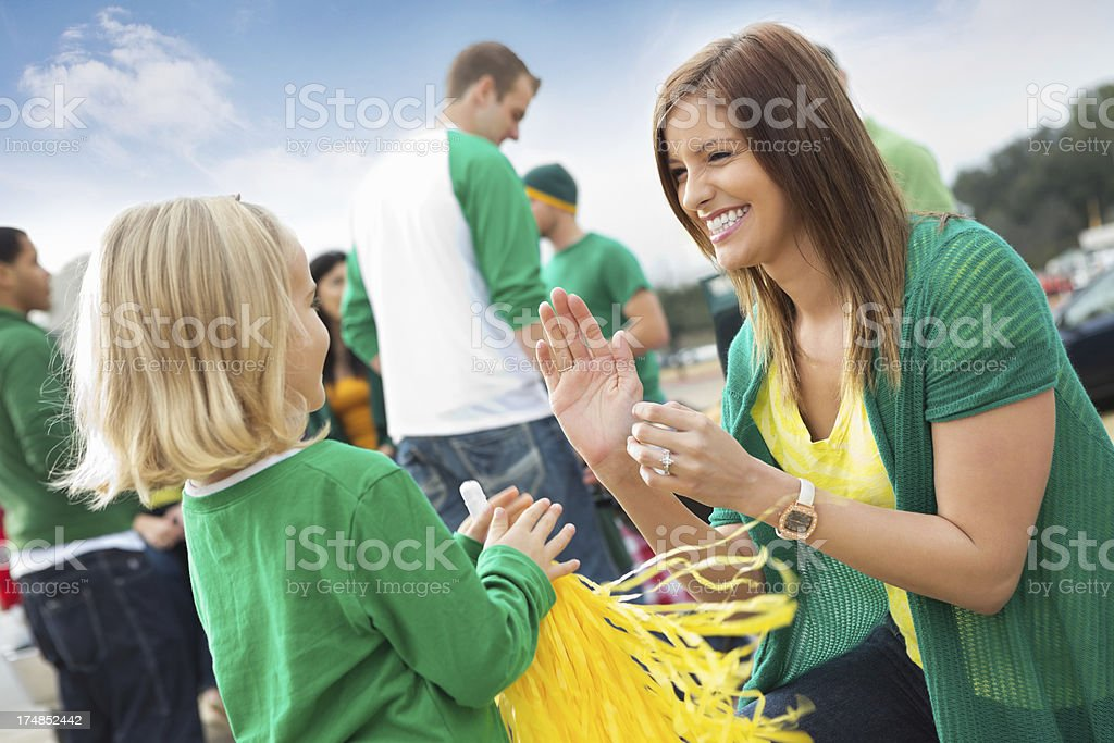 Mom and daughter cheering with friends tailgating at college stadium stock photo