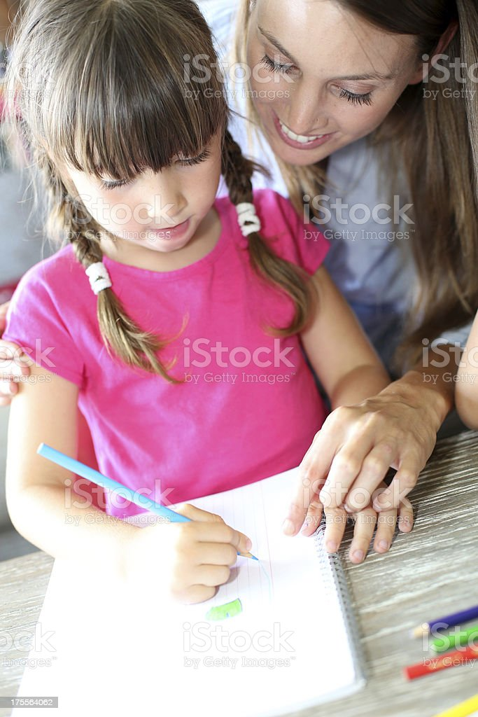 Mom and daughter drawing together at home royalty-free stock photo