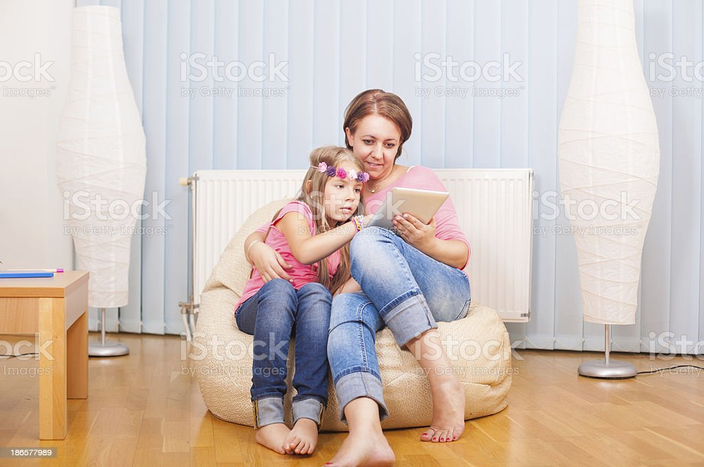 Mom and daughter have fun with notepad royalty-free stock photo