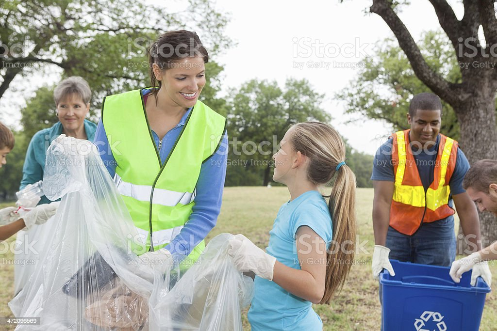 Mom and daughter helping clean up community park stock photo