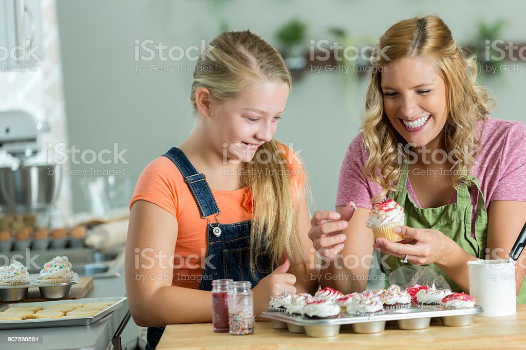 Mom and daughter laughing while they decorate cupcakes stock photo