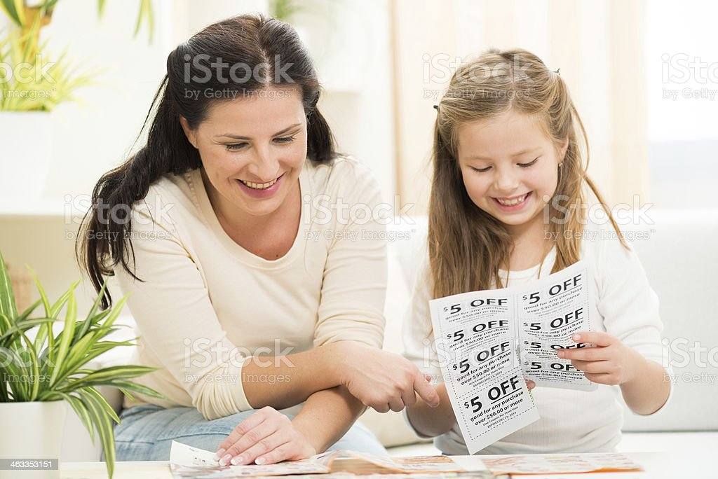 Mom and daughter making shopping list and cutting coupons stock photo