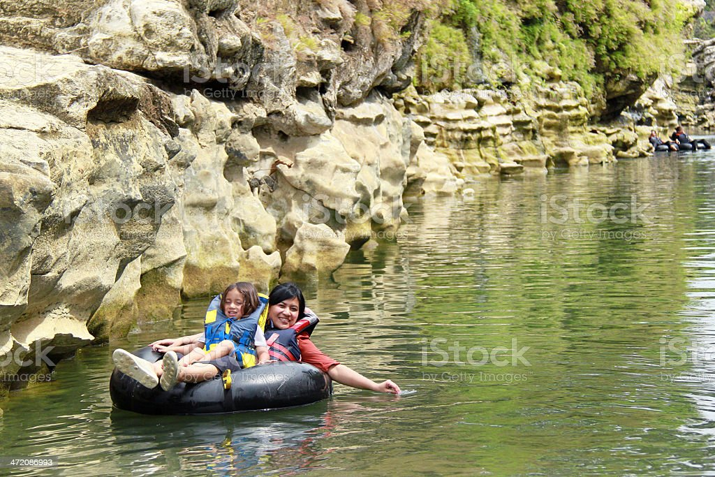 Mom and daughter on a black inflatable tube on a river stock photo