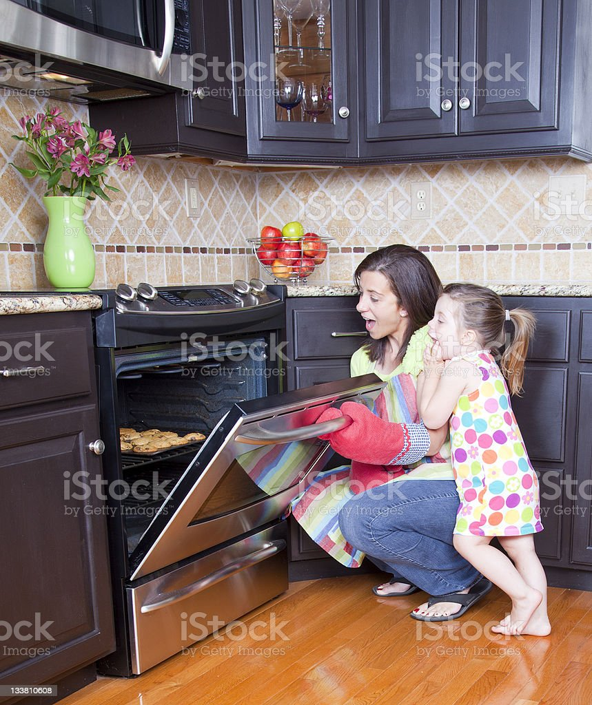 Mom and daughter opening oven to look at cookies baking stock photo