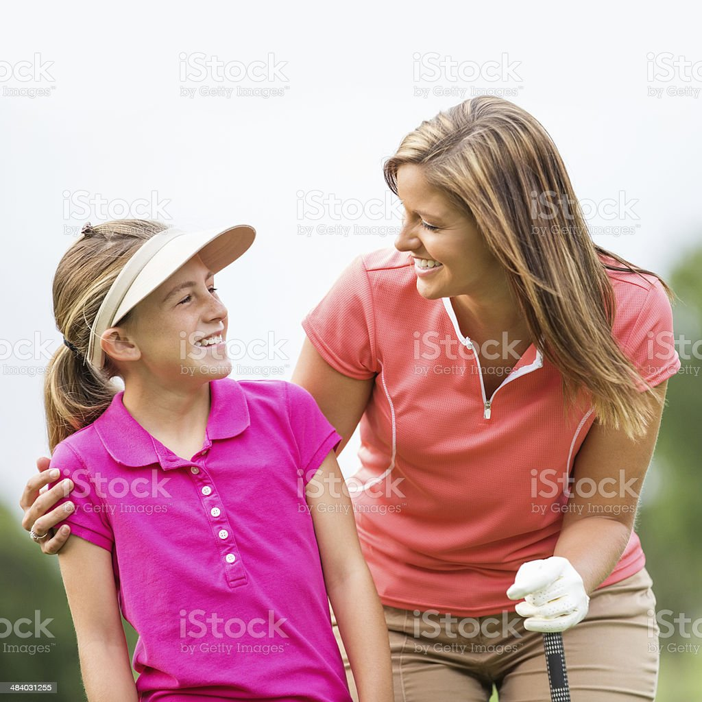 Mom and daughter playing golf together at country club royalty-free stock photo