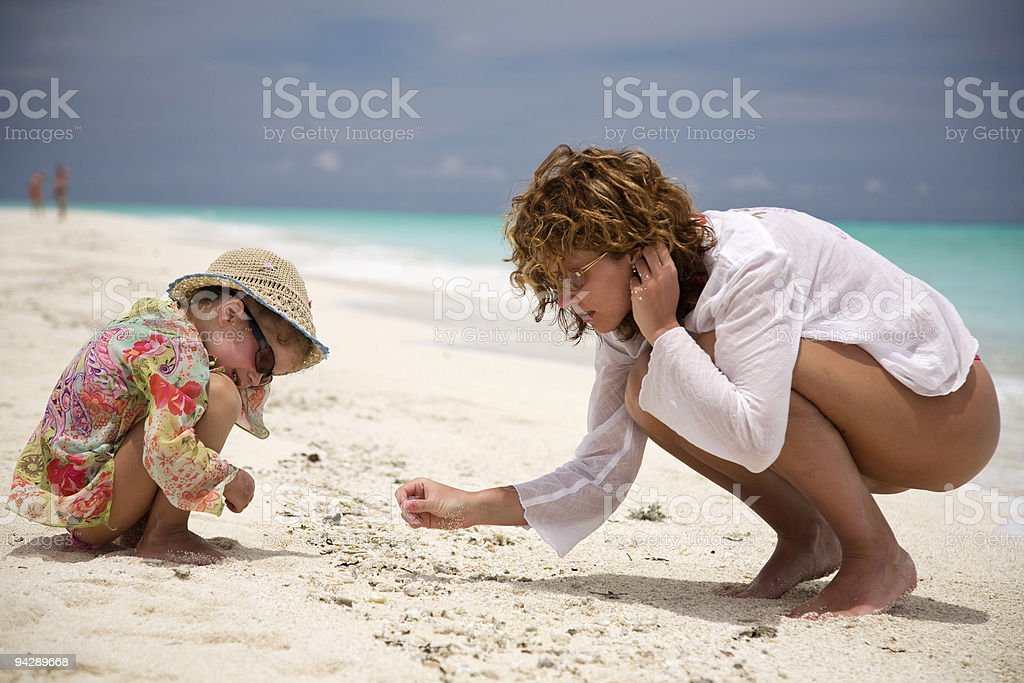 Mom and daughter playing on beach stock photo