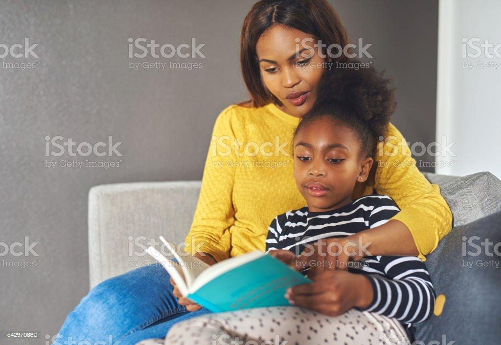 Mom and daughter reading a book stock photo