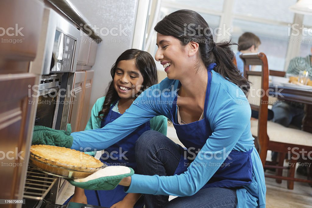 Mom and daughter removing apple pie from oven in kitchen stock photo