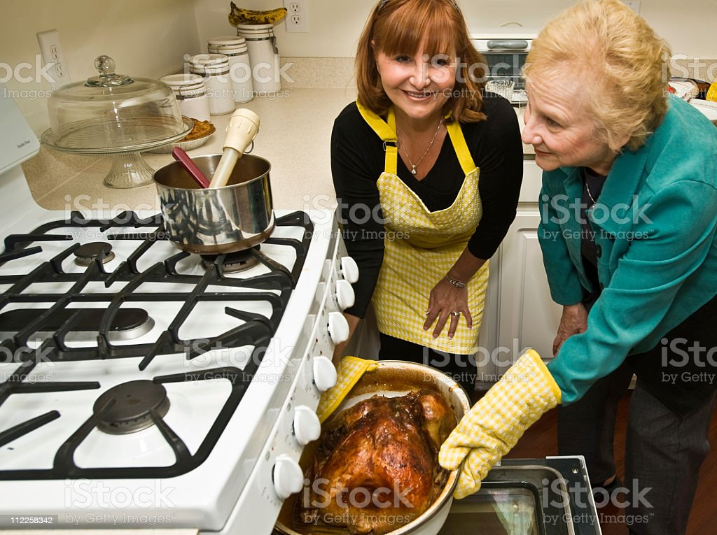 Mom and daughter taking a turkey out of oven royalty-free stock photo