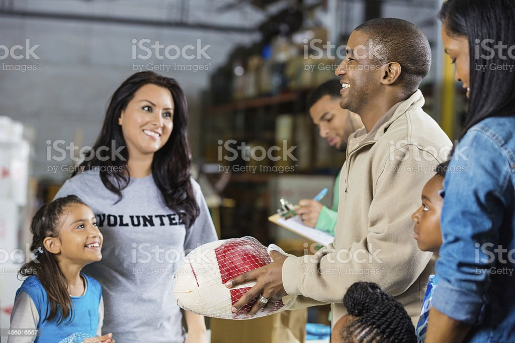 Mom and daughter volunteering to accept holiday food donations stock photo