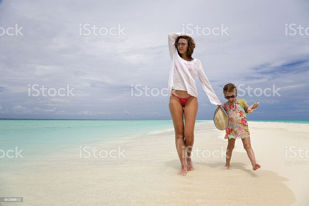 Mom and daughter walking on beach royalty-free stock photo