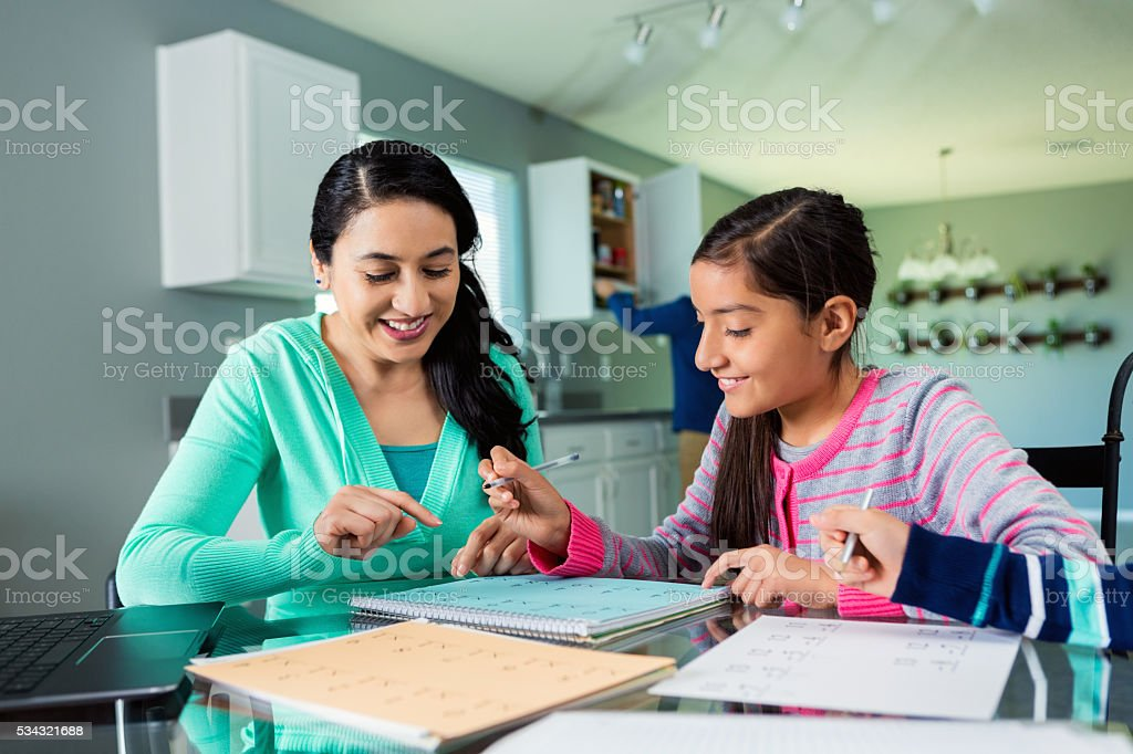 Mom and daughter work on homework stock photo