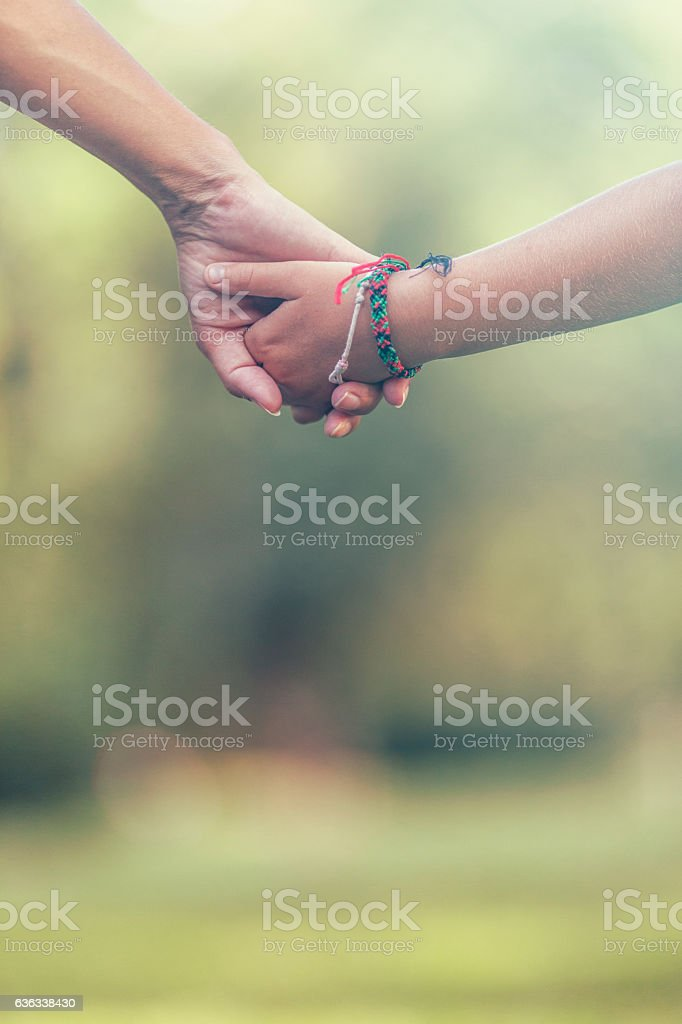 Mom and dauther holding hands stock photo
