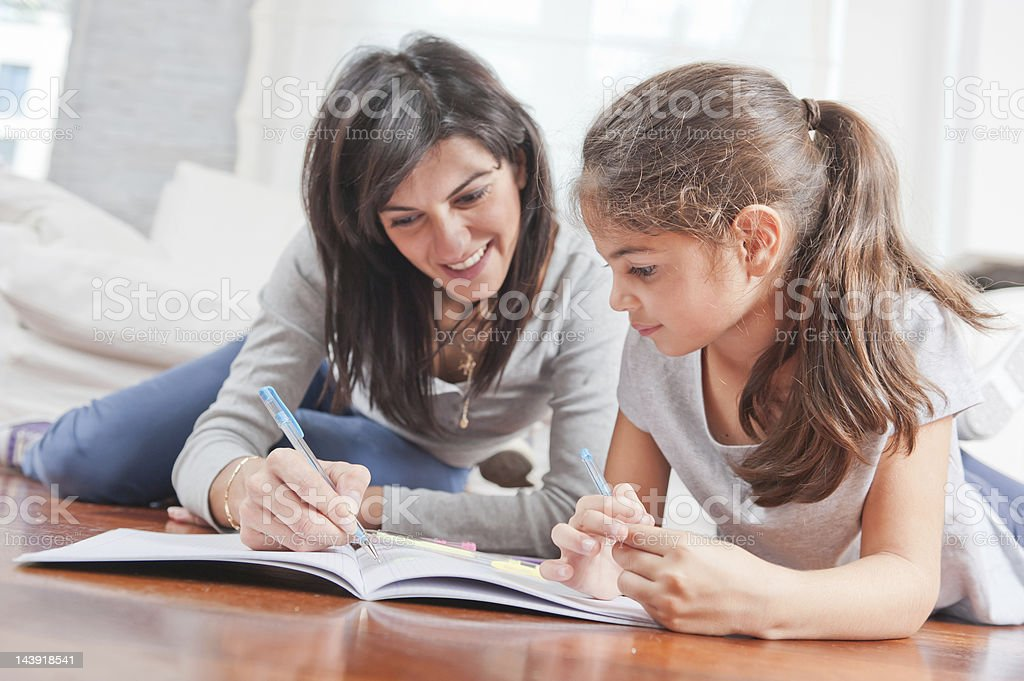 Mom and doughter writing together royalty-free stock photo